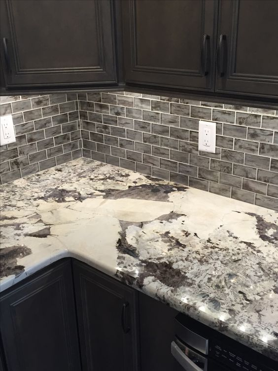 The white and black of the granite create a classy look that nearly matches the tiles on the back wall. With the black cabinets it's sure to add just the right amount of brightness.