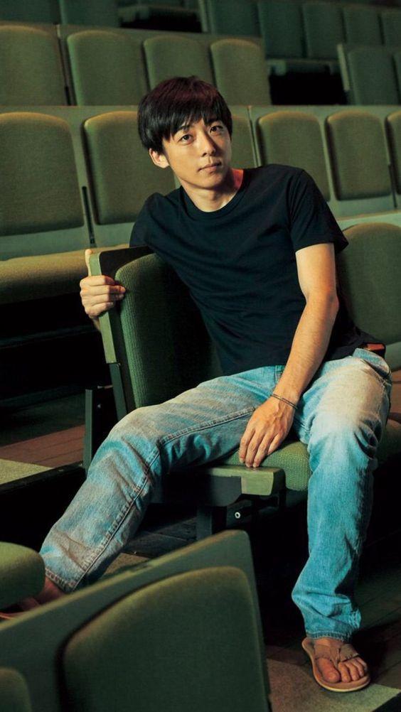 デニムをはいて映画館の客席に座っている高橋一生の画像