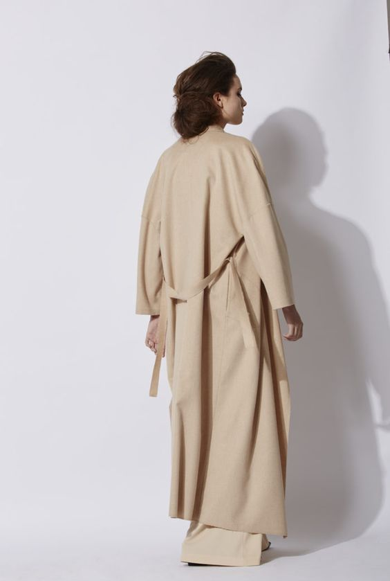 Nose Coat in beige: Long wool coat made of 100% baby camel. This model has no lining and a collar with wide lapels. The coat has pockets on the sides, and the finishings of the coat uncapped, with the outline stitching visible. This model is available in green and in beige. Made in Barcelona. Cortana AW 2016 collection. Shop online.