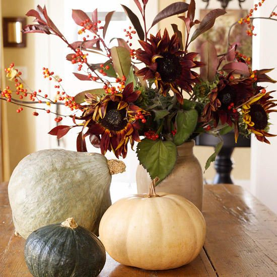 A pumpkin and gourds complement an urn filled with an autumnal arrangement of red sunflowers and leaves. The muted colors of the pumpkin and gourds allow the bold sunflowers to steal the show in this fall centerpiece.