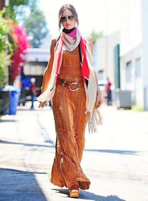 Alessandra Ambrosio saca su lado más hippie gracias a este vestido calado en naranja que combina con cuñas de madera, cinturón de piel y fular tricolor. #moda #fashion #cuero #leather #zapatos #shoes #bolsos #bags #marroquineria #leathergoods #estilo #style #lifestyle
