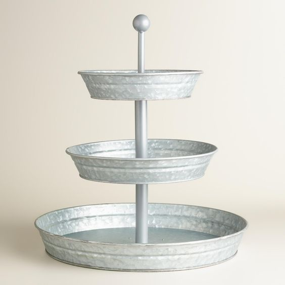 Featuring three raised layers with tall edges to prevent accidents, our exclusive metal caddy stand is a compact centerpiece for snacks and treats with a loop handle for easy, level transport. >> #WorldMarket Kitchen Tools and Storage, Kitchen Decor, Tips