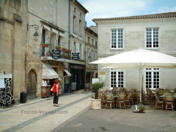 Saint-Émilion: Place avec maisons bordées de boutiques et d'une terrasse de café - France-Voyage.com - Porte cochère de l'entrée du cloître de St-Emilion.
