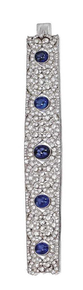 ART DECO CABOCHON SAPPHIRE AND DIAMOND BRACELET, VAN CLEEF & ARPELS, PARIS, CIRCA 1930. The slightly tapering openwork band set at intervals with 6 cushion-shaped cabochon sapphires within a pattern of foliate springs and confronting C-scrolls, set with 390 round, old European-cut and single-cut diamonds weighing approximately 24.00 carats, mounted in platinum, length 7¼ inches, signed Van Cleef-Arpels, maker's mark, assay marks.