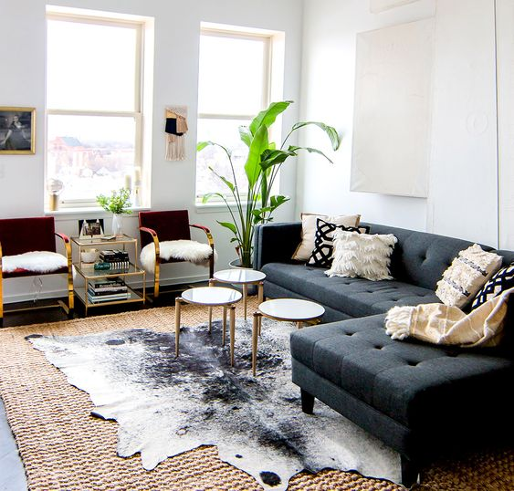 Gray sofa with modern coffee tables, cowhide rug, and indoor plants. I love the layering of the rug!!: