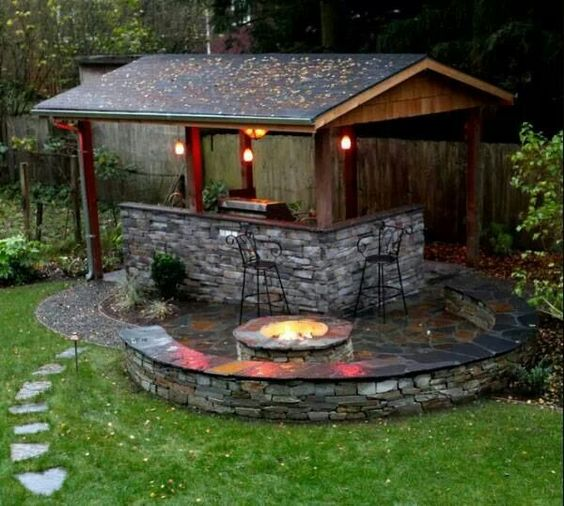 Outdoor kitchen with fire pit half circle wall with for Outdoor cooking area and fireplace
