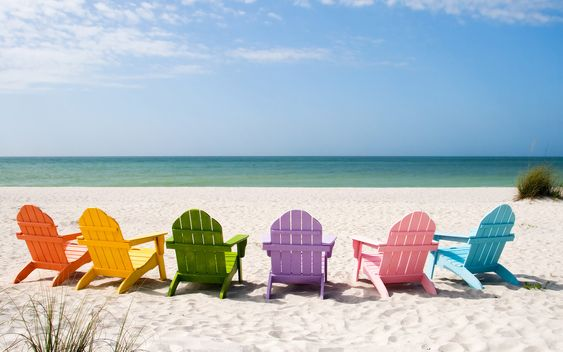 a rainbow of Adirondak chairs at the beach