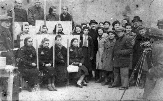 Lodz, Poland, 1942, Jews being photographed for work permit pictures in the ghetto. Jews are sitting in rows, and a photographer is photographing their faces for the purpose of issuing work permits in the Lodz ghetto in 1942
