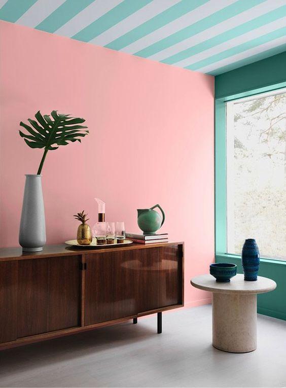 Rose Quartz, ou Rosa Quartzo, foi escolhida como a cor do ano de 2016! Ela caiu muito bem nessa parede, e o contraste com o aparador de madeira vintage e o teto listrado de turquesa ficou ótimo, não é mesmo? Confira mais 19 ambientes com o tom clicando na imagem! <3: