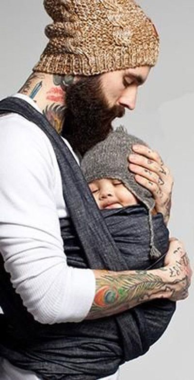 Tattooed bearded dad with his little baby could he for Daddy carrier