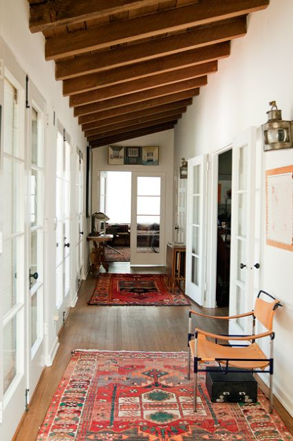 exposed beams, white walls, worn ethnic rug