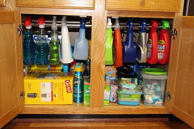 Use a tension shower curtain rod (only $8!) under the sink for hanging bottles of cleaner. This blog has other great kitchen organizing tips!: