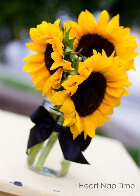 This bright arrangement is a great example of a simple DIY centerpiece. A few sunflowers in a jar, a ribbon tied around, and done!