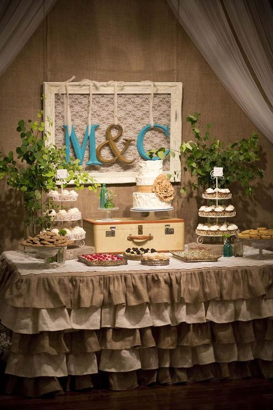 Burlap ruffled adorn a vintage A leather suitcase elevates a three-tiered cake.  A pair of cupcake stands balances the display....:
