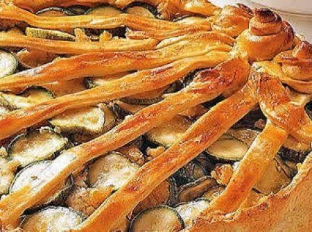 Receita de Empadão de Abobrinha - 2 e 1/2 xícaras (chá) de farinha de trigo, 1 colher (chá) de sal, 3/4 de xícara (chá) de manteiga gelada em pedacinhos, 1/3 de xícara (chá) de água gelada., 1 cebola grande picada, 4 dentes de alho picados, 6 fatias de toucinho defumado picadas, 12 fatias de pão de forma sem casca trituradas no processador, 1 colher (sopa) de manjericão picado, 2 colheres (sopa) de vinagre, 5 abobrinhas médias cortadas em rodelas de 0,5 cm de espessura, 1 colher (sopa) de…