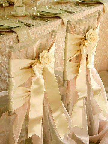 For the Bride and Groom  Honor the bride and groom with a unique treatment for their chairs. Here, an abundance of coral-color organdy fabric is draped over the chairs and fashioned into unstructured slipcovers. The no-sew covers are held in place with elegant, double-face satin ribbon. Fresh flower corsages are pinned to the chair backs.