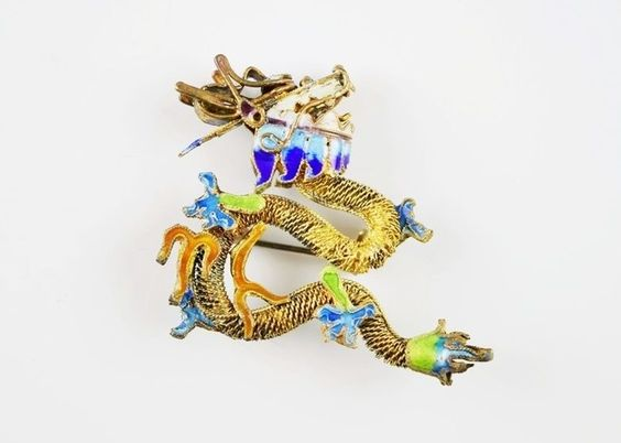 A stunning vintage sterling silver gold gilt Chinese dragon brooch with colorful enamel detailing. The serpentine body of the dragon is done in filigree with enameled work and a beautifully detaile...