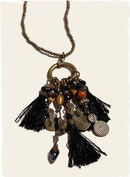 O colar de contas de bronze pendurado encantos variados e borlas de um pingente anel de bronze.