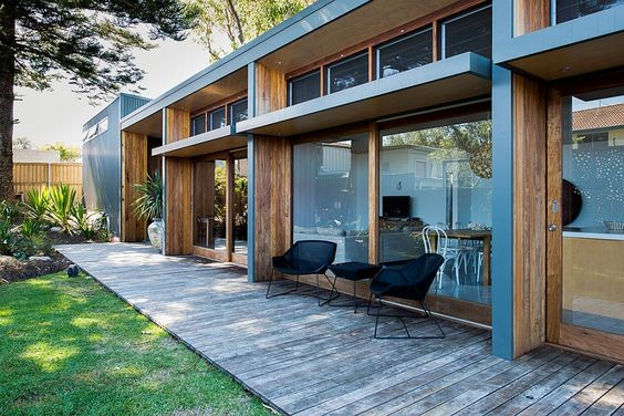 Glass windows open up the interior to the backyard Small 70s Home in Australia, Gets Creative, Eco Friendly Extension