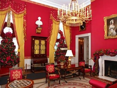 Red lacquered magnolia leaf wreaths in the windows of the White House Red Room.