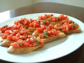 Bruschetta with tomato and basil.  Chopped fresh tomatoes with garlic, basil, olive oil, and vinegar, served on toasted slices of French or Italian bread.