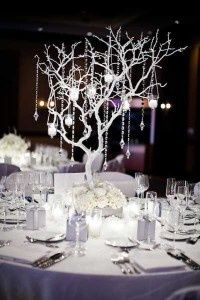 Spraypaint branches silver and add glitter? Then maybe hang glitter pinecones and crystals from the branches, and make the bases look like snow. Then surround them with tealights set in aqua, clear, and mint glass marbles.