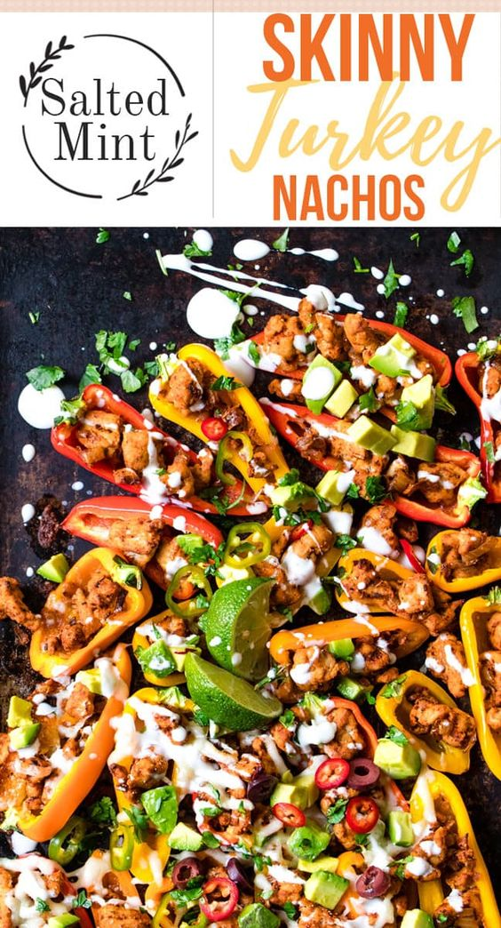 These gluten-free nachos are the perfect solution to healthy game day snacks. Spicy Cajun turkey is stuffed into mini bell peppers and baked with cheese. Fully loaded with chilies, avocado and lime crema these are a guilt-free snack. #gamedayrecipes #nachos #glutenfreesnacks