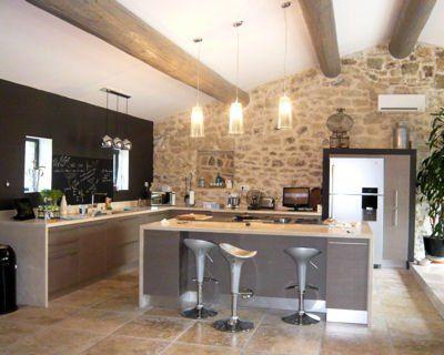 Belle cuisine ouverte avec îlot central, poutres effet lasuré et mur en pierres de parement.