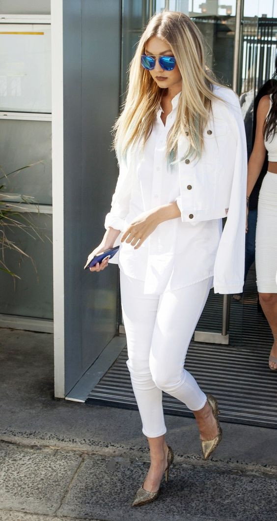 Gigi Hadid wears a white button-down blouse, denim jacket, white cropped skinny jeans, neutral pumps, and mirrored sunglasses: