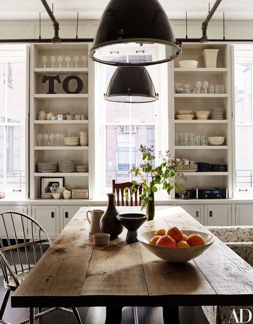 White kitchens design ideas: Meg Ryan's industrial farmhouse style white kitchen in her New York apartment. Open shelves, black pendant lights, and rustic warm wood farm table. #farmhousekitchen #industrial #farmtable #modernfarmhouse #blackandwhite