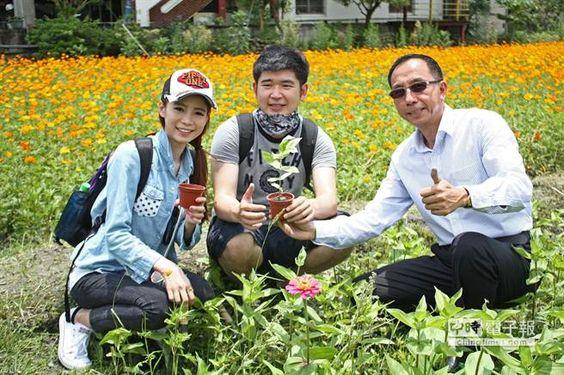 【三星鄉美麗花海將翻耕 提供免費挖花】  來自台北的情侶檔李奇灃(中)和姜佩琪(左),路過花海下車拍照,三星鄉長黃錫墉(右),熱情歡迎他們把花帶回家。(王亭云攝)