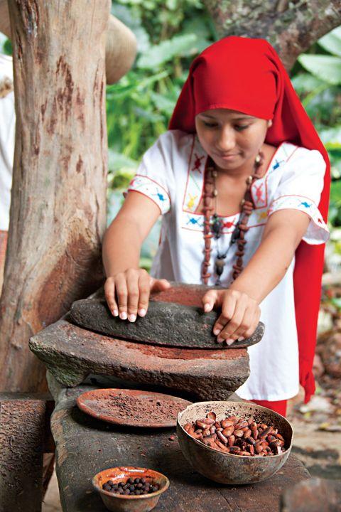 Choca moliendo granos de cacao en metate.