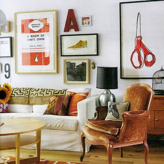 Eclectic gallery wall with velvet antique armchair