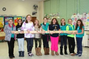 Members of Girl Scout Troop 70106 holding one of the wood beams they decorated for a new home being built by Habitat for Humanity.