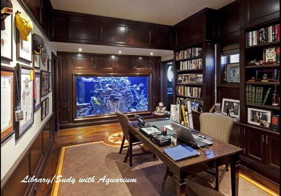 """Shark Tank Home Office, Malibu, California To focus on business instead of the scintillating water views in this oceanfront mansion, the owner had a 1,000 gallon salt-water aquarium installed in his home office. It's """"an obvious yet calming reminder of the ocean."""" That's if you aren't distracted by the feeding schedule of a leopard shark, a three-and-a-half foot long yellow mouth moray eel, a blue spotted sting ray, harlequin tusk, star fish and a mappa puffer. YES I LIKE!"""