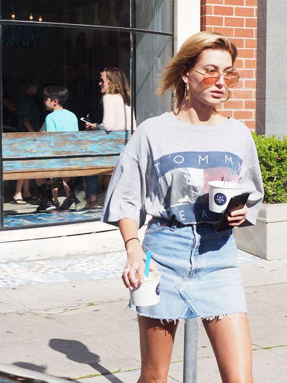 Hailey Baldwin usa saia jeans com maxi t-shirt e óculos coloridos