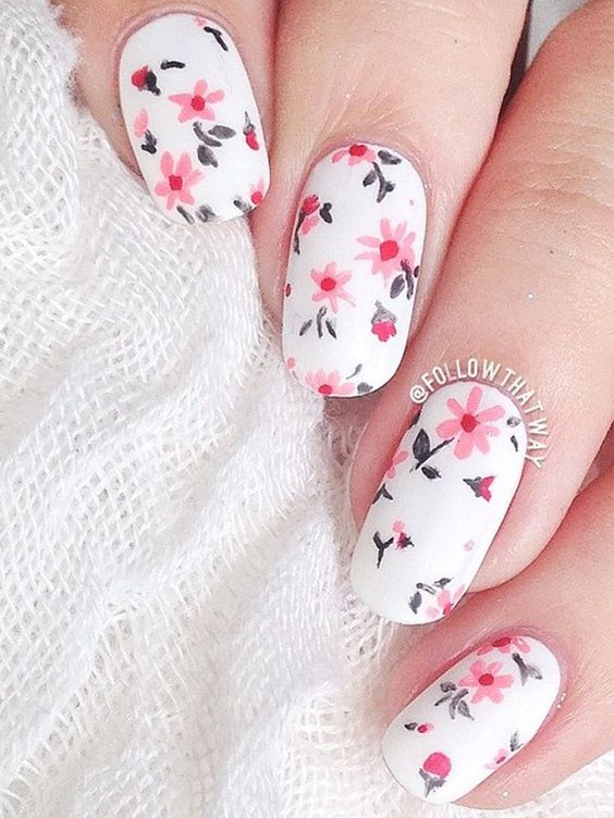 Give your nails a bright spring feel with this flower inspired nail art design. The falling pink flowers look perfect against the white base color of the nails.