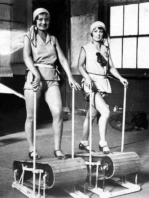 Working the treadmill, circa 1920. Complete with ballet shoes, these women look glamorous and very stylish in their workout garb. These machines are made of wood and steel and are 100% human powered. Running a mile must have felt like 5.: