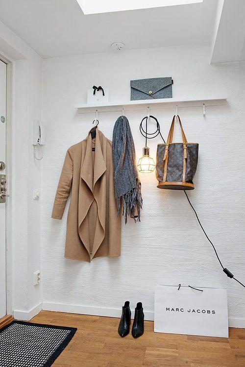 prateleira com ganchos para pendurar casaco, cachecol, bolsa no hall de entrada da casa, sacola amarc jacobs no chão: