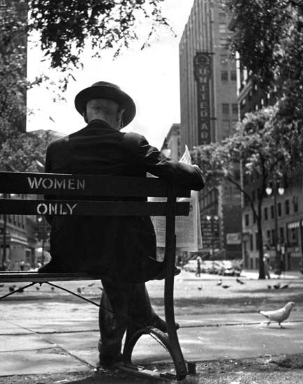 A man sits on a bench in Grand Circus Park in the summer of 1958, oblivious to the posting on the chair. (Detroit News Archives)