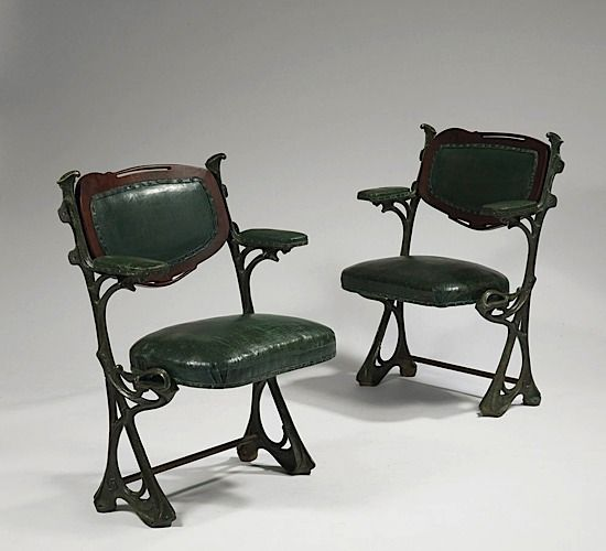 Hector GUIMARD chairs c1905. A pair of seats from the Humbert de Romans  concert hall, Paris.  Cast iron with green patina and curved mahogany backrests and moleskin covers.