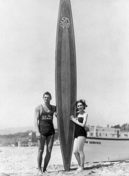 Johnny Weissmuller And The Actress Maureen O'Sullivan  with a Santa Monica Lifeguard board on Santa Monica Beach - ca 1930 - Getty Images 106752295