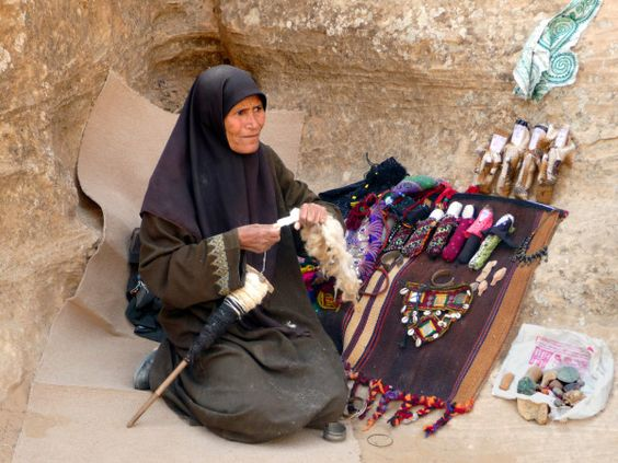 Jordanian spinner.  How does she turn the spindle? Looks like against her leg as too big to have suspended.