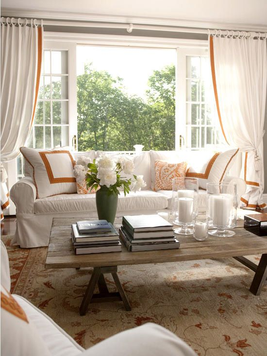 A monochromatic palette plus one accent hue is a simple way to create a chic, pulled together room. In this family room, bold bands of orange line curtains and embellish throws pillows, sketching a graphic outline. A floral rug rendered in rusty oranges and browns and a coffee table crafted from stained 1x4s introduce a toasty warmth that balances the crisp coolness of the white sofas.