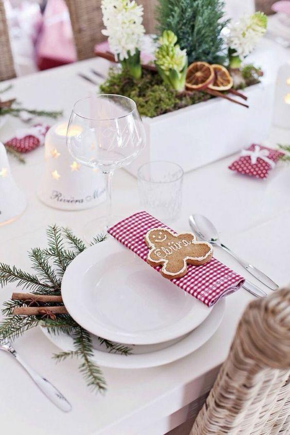 déco table Noël rouge et blanc - vaisselle blanche, serviettes à motif vichy en rouge et blanc, biscuits bonhommes et un centre de table composé de mousse, tranches d'agrumes, cyprès et fleurs blanches