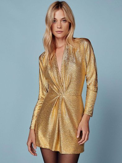 Be the disco ball. This is a mini length dress with a low v neckline and long sleeves.