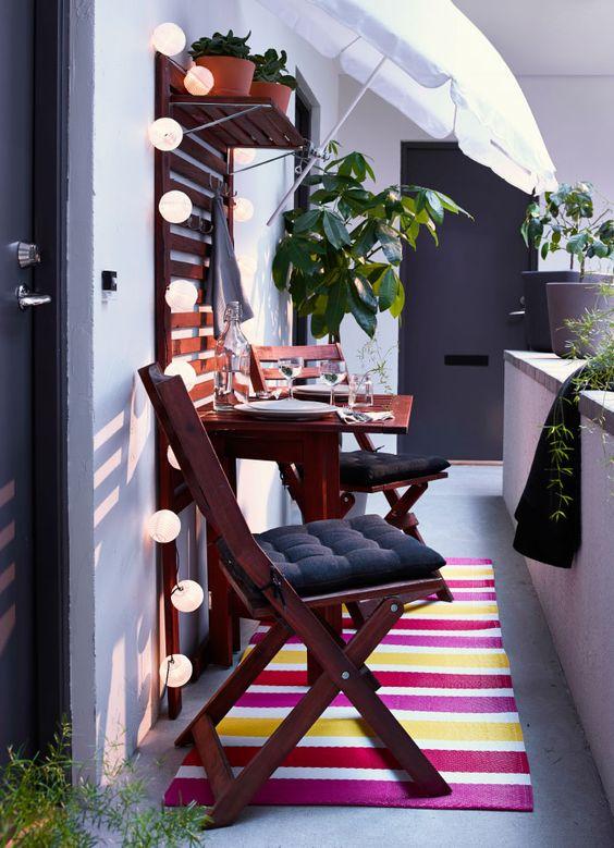 Sedie pieghevoli e tavolo a ribalta marroni. Pannello da parete in legno con ripiani e illuminazione decorativa.