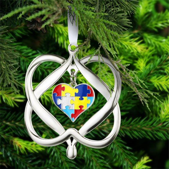 The colorful puzzle piece of autism awareness is framed within two intertwined hearts on our touching Christmas ornament.