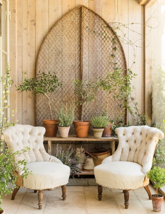 Deconstructed linen tufted chairs on a porch with a rustic table of topiaries and potted herbs. #patinafarm #frenchcountry French farmhouse french country porch - Patina Farm by Brooke Giannetti.