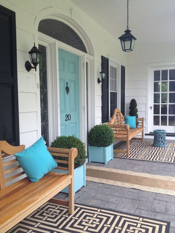 Front porch design with chippendale benches, turquoise front door and planters.: